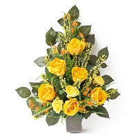 Bouquet of yellow roses and daisies In plastic, with decorative foliage